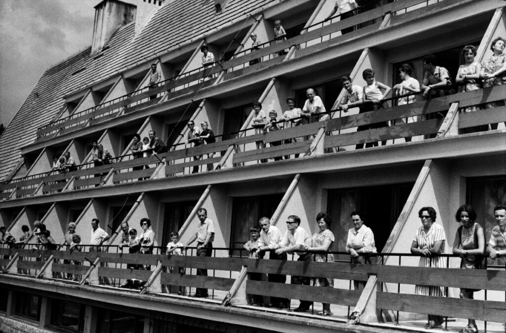 People posing to the group photograph on the hotel balconies.