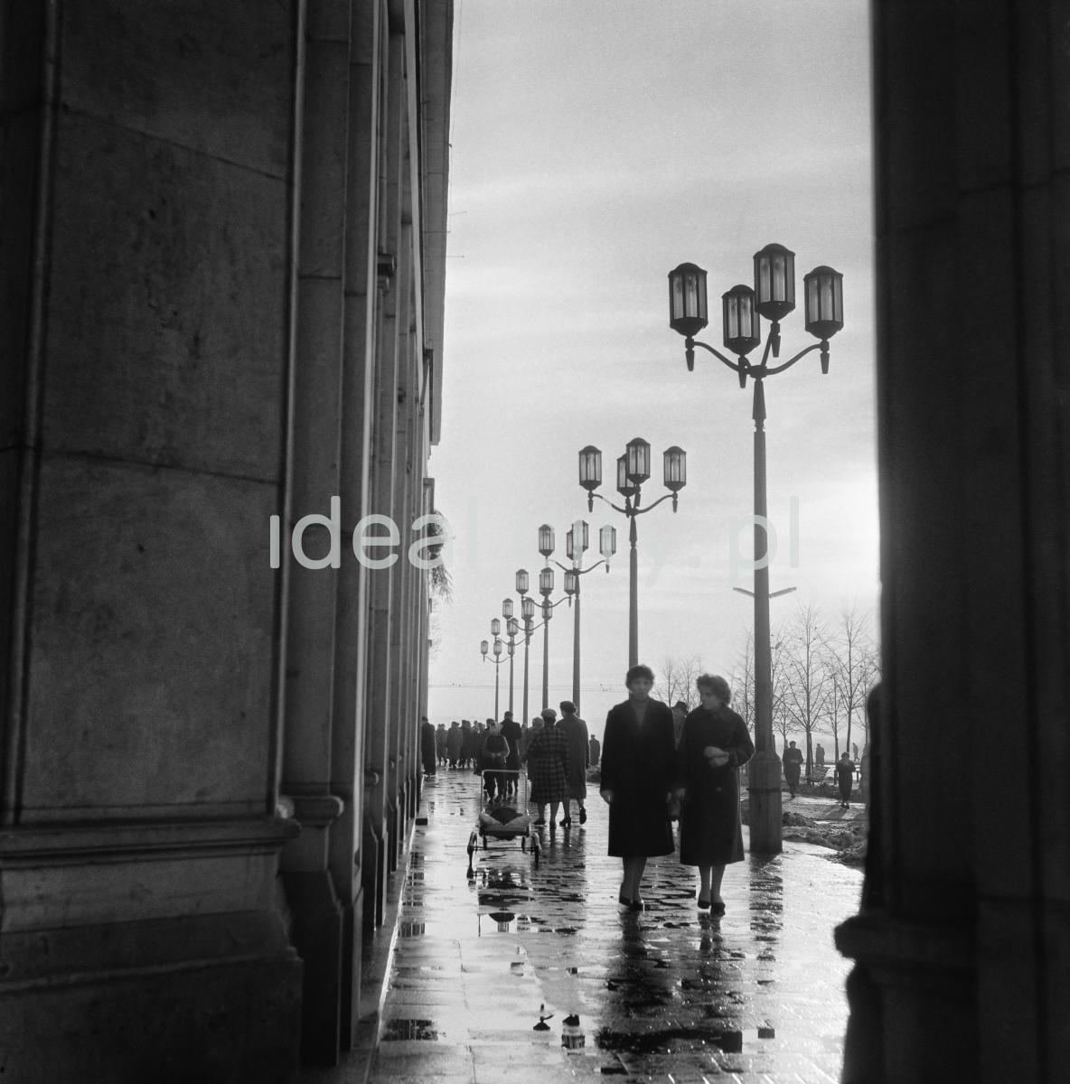 Ruch pieszy na reprezentacyjnym deptaku pomiędzy socrealistycznym budynkiem a monumentalnymi latarfniami ulicznymi.