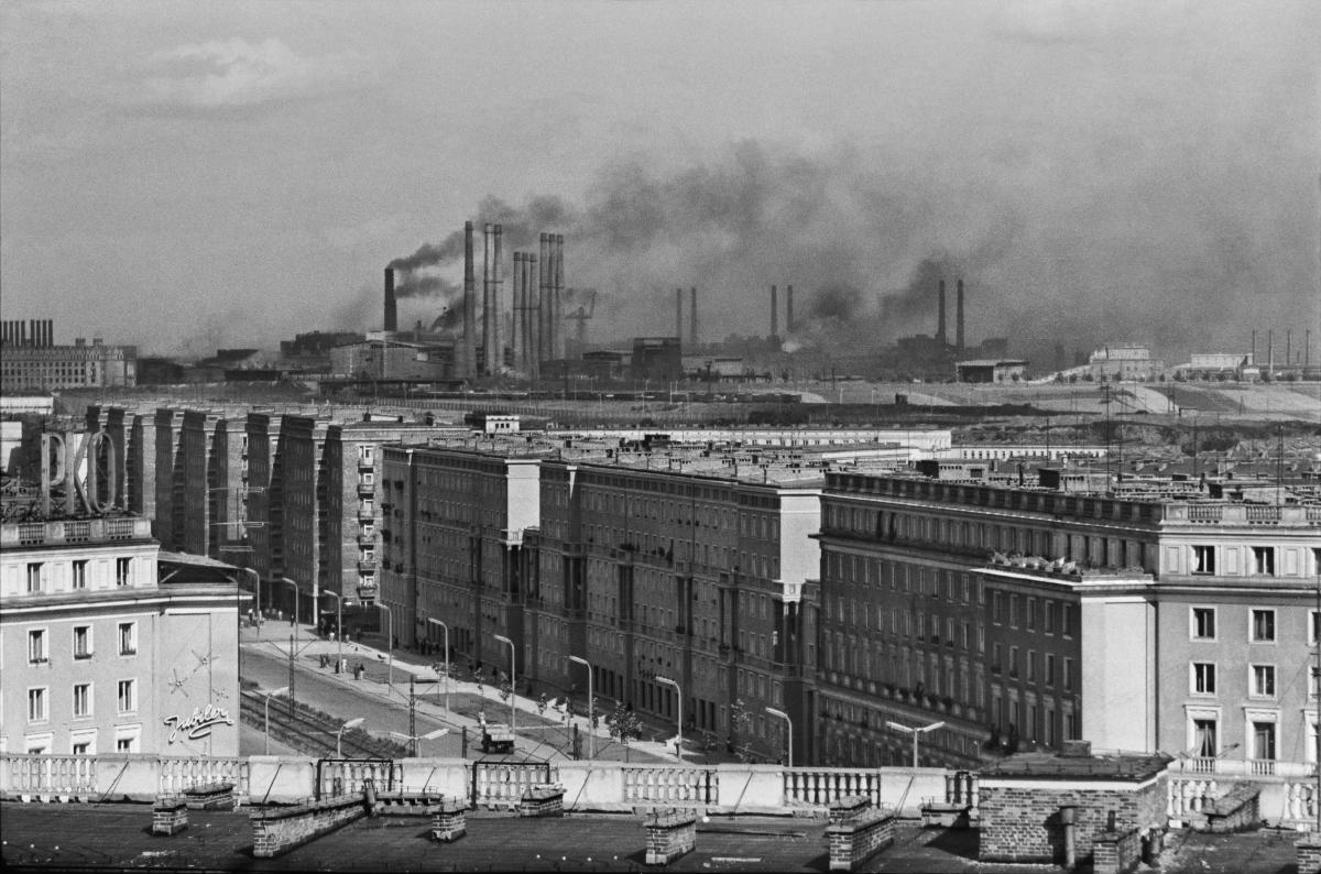Perspektywa miasta w kierunku kombinatu wykonana z wysokiegoi piętra budynku. Za szeregiem masywów budynków mieszkalnych górują wysokie kominy, z których ulatuje ciemny dym spowijający miasto.