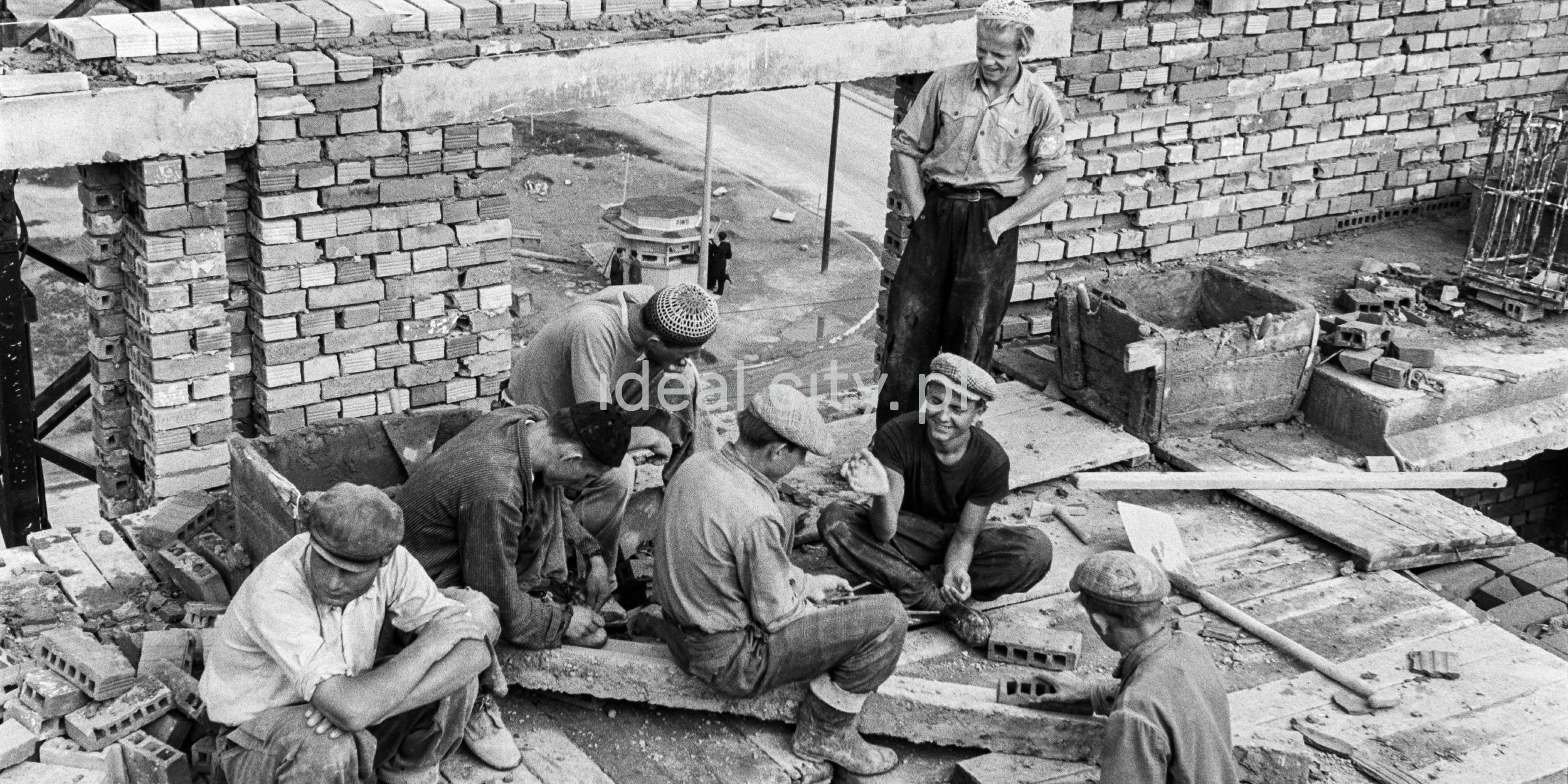 Grupa robotników w trakcie przerwy na nowo budowanej kondygnacji budynku. W perspektywie ulicy widoczna budka z piwem.