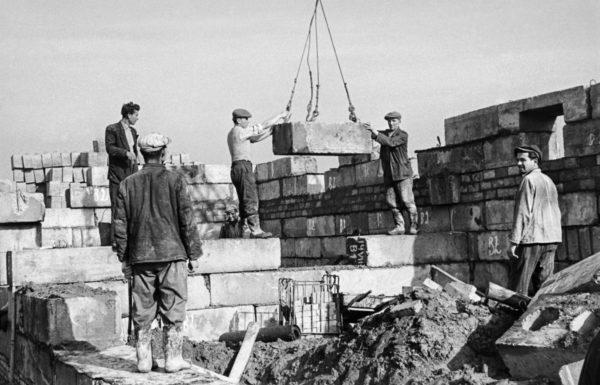 Dwóch robotników koordynuje ręcznie pracę dźwigu przenoszącego prefrabrykowany blok betonowy. Trzech pozostałych przygląda się.
