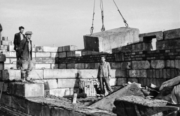 Dźwig przenosi prefabrykowany element betonowy, czemu przygląda się trzech robotników.