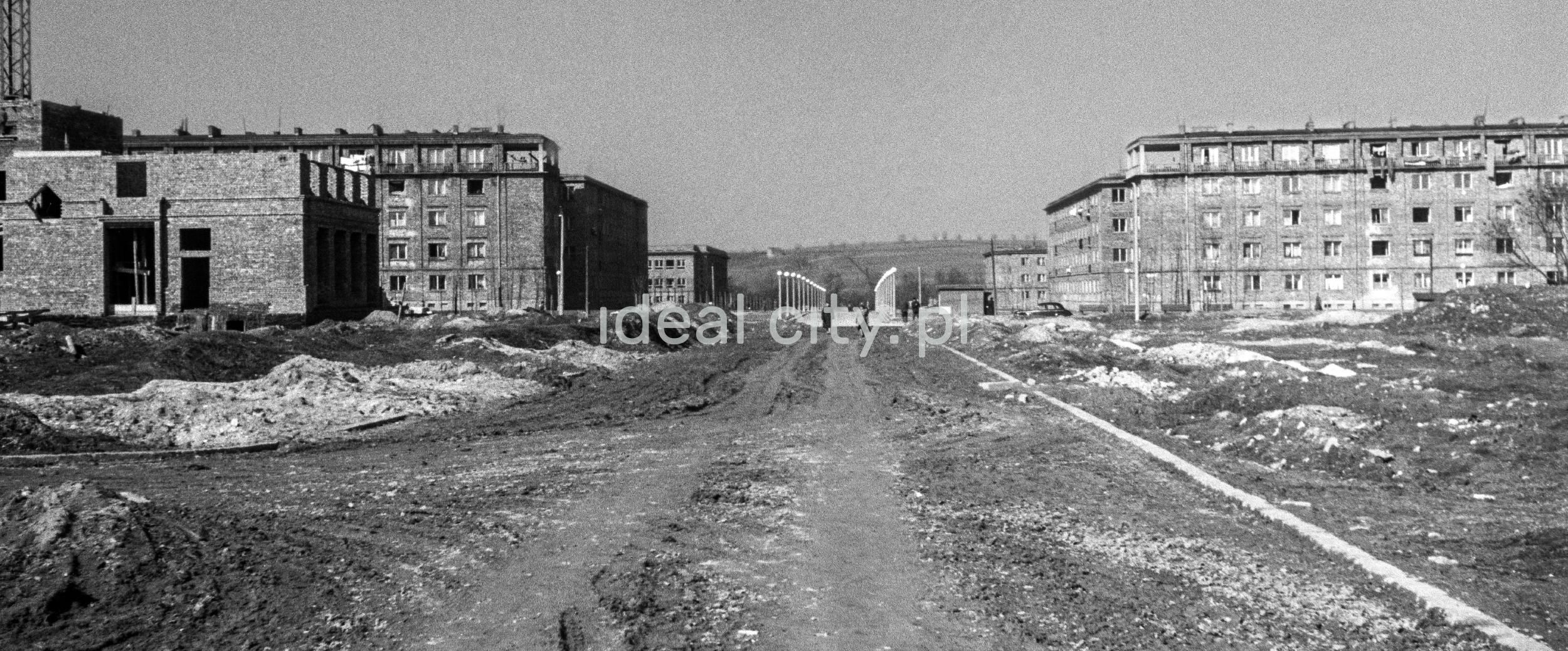Centralne, perspektywiczne ujęcie szerokiej alei w budowie, w tle, po lewej i prawej stronie ukończone budynki osiedli mieszkaniowych.