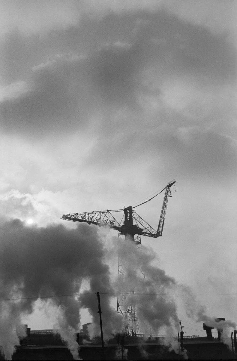 Pionowe ujęcie, pod światło. Przez dym wydobywający się z kilkunastu kominów na pierwszym planie przeziera żuraw budowlany.