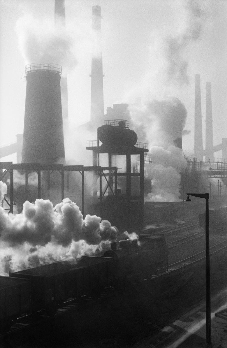Pionowe ujęcie na dymiące intensywnie różnej wysokości i średnicy kominy. Krajobraz domyka na pierwszym planie ciągnąca skład węgla lokomotywa.