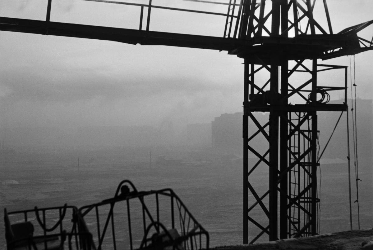 Ujęcie teleobiektywem z dużej wysokości, w stronę południową. Na pierwszym planie zarys żurawia budowlanego przez, który widzimy plac budowy osiedli. Widoczność mimo słonecznego dnia utrudnia zimowa mgła.