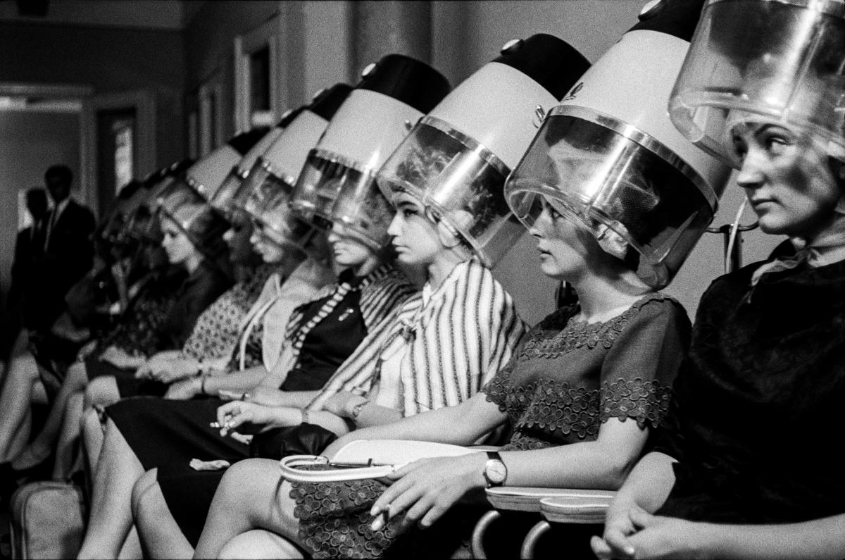 Kilkanaście kobiet siedzących w szeregu utrwala fryzury pod kloszami suszarek.