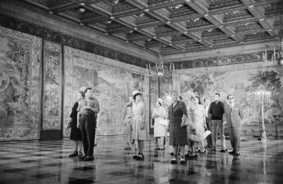 Grupa osób w strojach wizytowych na środku pustego pomieszczenia jednej z komnat królewskich.