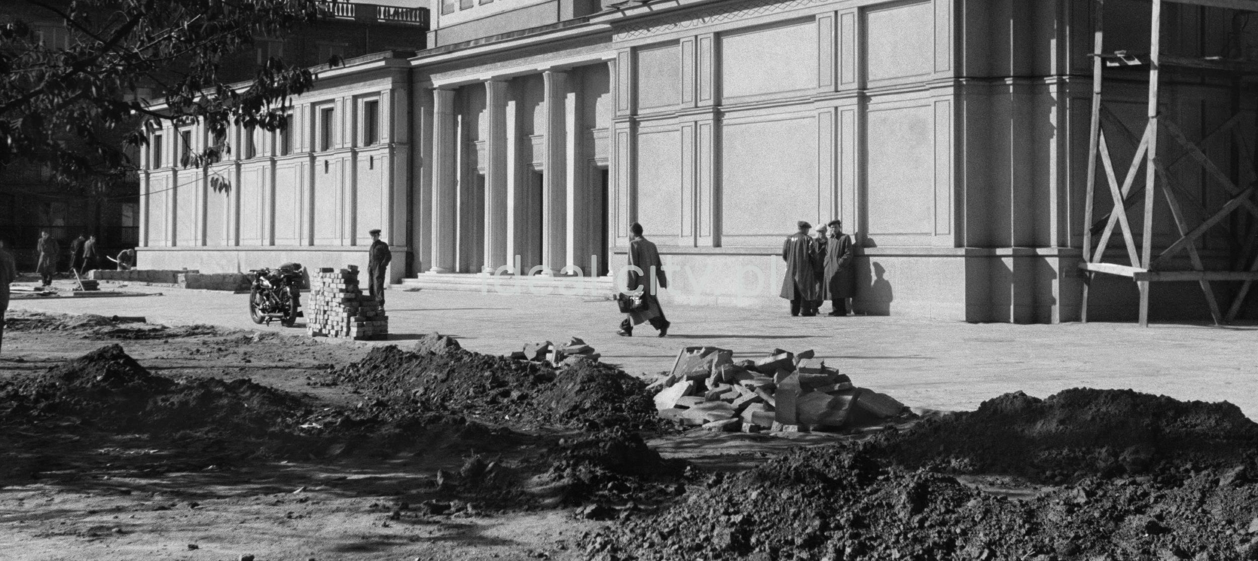 Mężczyźni w płaszczach pod ścianą wykańczanego właśnie monumentalnego budynku teatru.