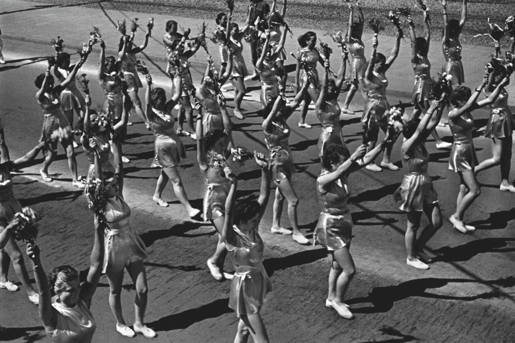 Młode kobiety w strojach sportowych maszerują wykonując ćwiczenia gimnastyczne.