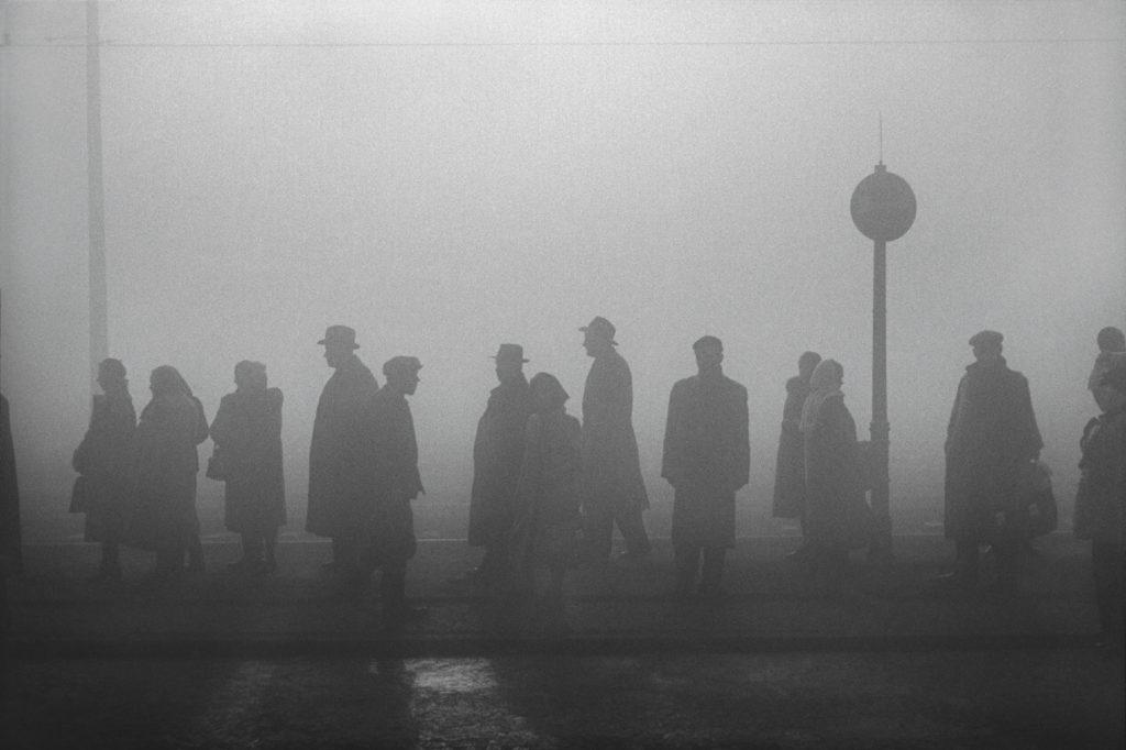 Postaci w płaszczach i kapeluszach stoją we mgle na przystanku tramwajowym.