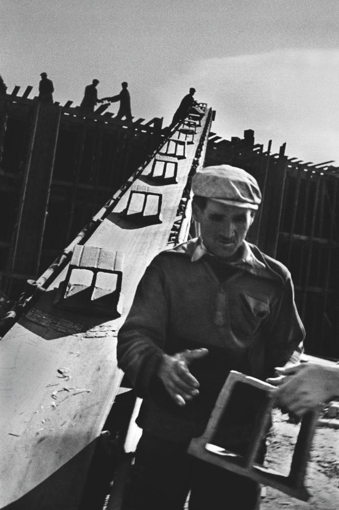 Murarze podają i odbierają cegły z taśmociągu.