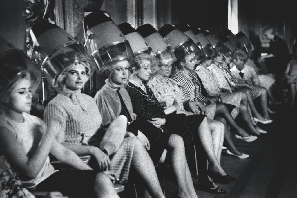 Kobiety siedzą w rzędzie pod fryzjerskimi suszarkami do włosów.