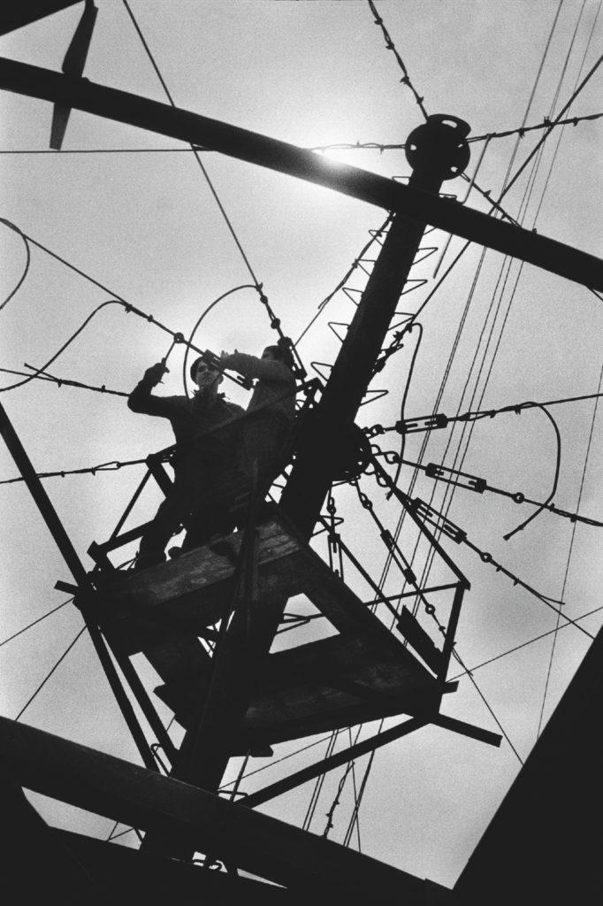 Ujęcie pod słońce przedstawia pracowników montujących na wysokim słupie stalowe liny.