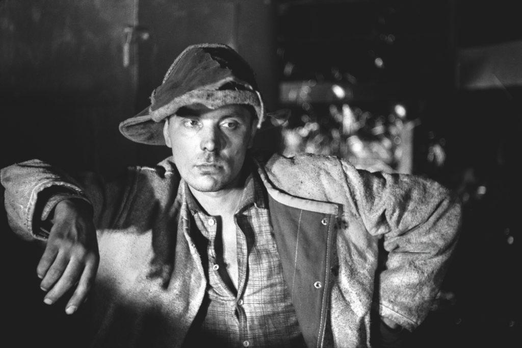 Portret hutnika opartego łokciem o sprzęt w hali fabrycznej.