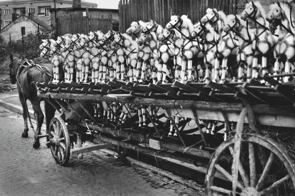 Rząd drewnianych koników na wozie zaprzągniętym w konia.