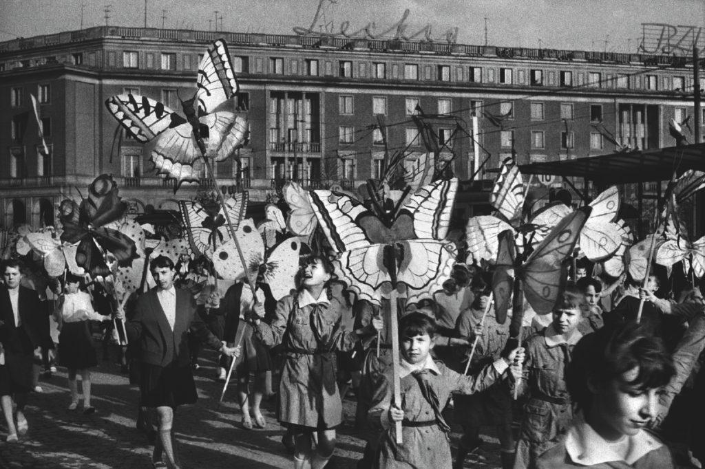 Dzieci maszerują w pochodzie niosąc tekturowe motyle.