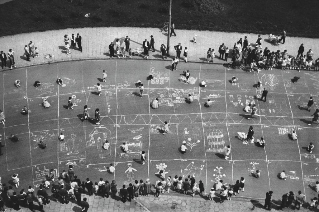Ujęcie z góry na dzieci rysujące kredą po asfalcie.