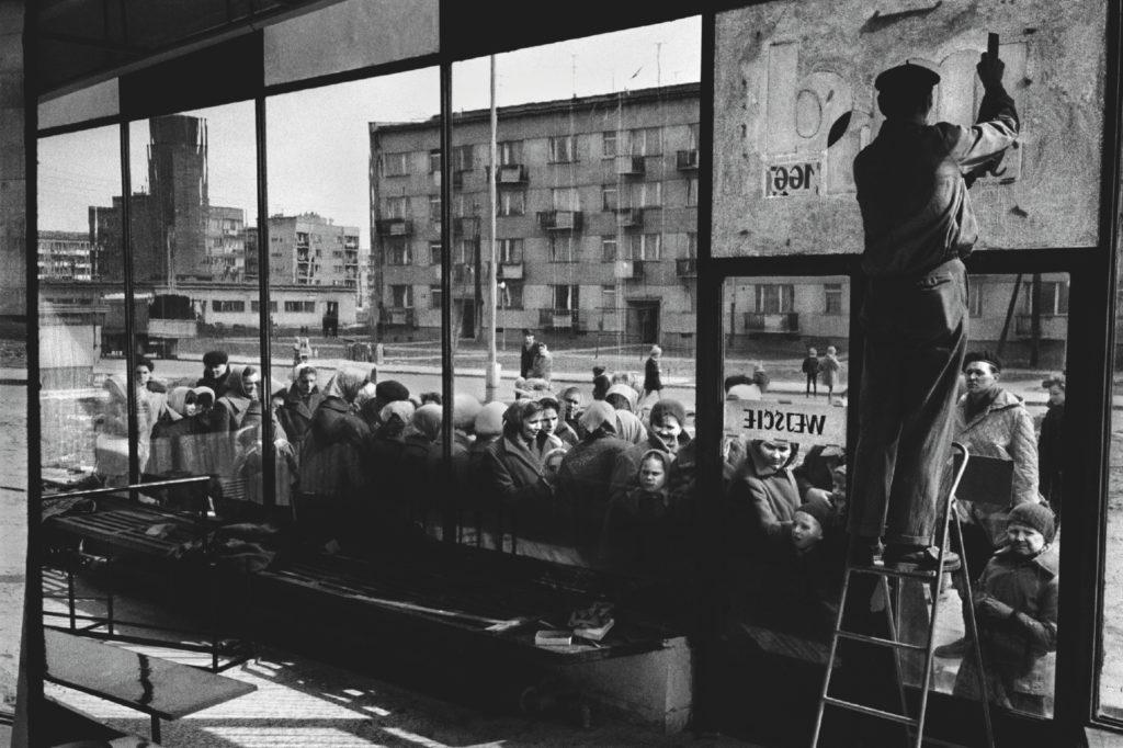 Ujęcie z wnętrza pawilonu sklepowego na ludzi stłoczonych w kolejce na zewnątrz.