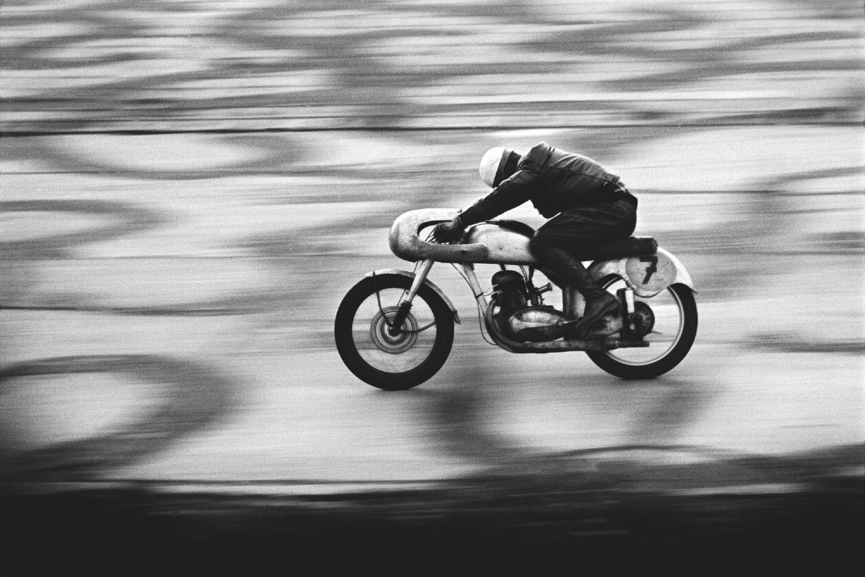 Pochylony na motorze motocyklista pędzi na motorze. Strój zawodnika jak i nowoczesny dizajn motocykla wskazują na lata 50. XXw. Zdjęcie dynamiczne przez zastosowanie dłuższego czasu naśwtietlania a przez to poruszone tło.