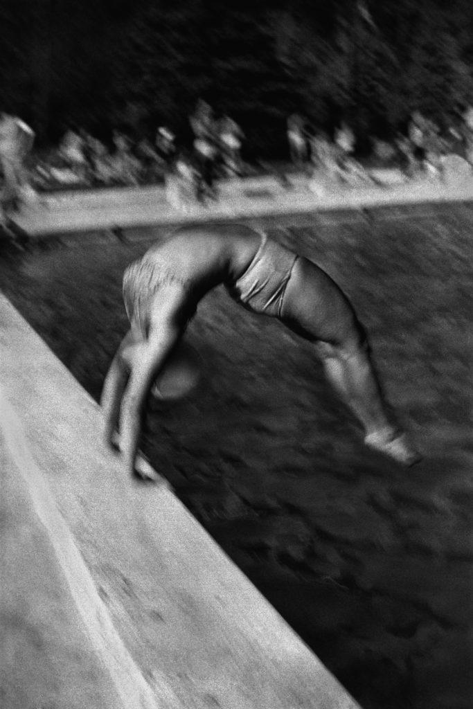 Postać w stroju kąpilowym skacze tyłem do basenu.