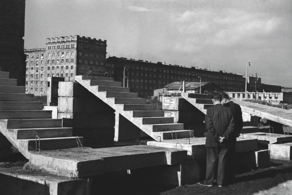 Dwóch mężczyzn w garniturach ogląda prefabrykowane schody wyeksponowane na wolnym powietrzu, przed blokami mieszkalnymi.