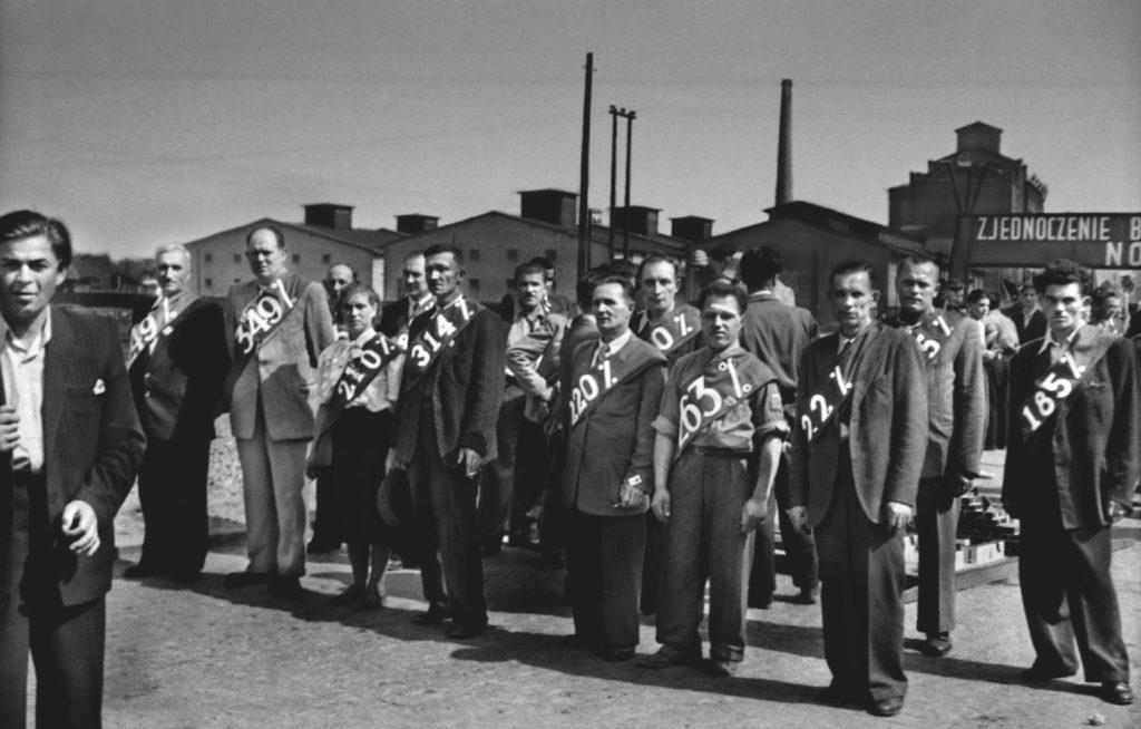 Mężczyzni w garniturach, przepasani harfami z napisami określającymi wypracowany przez nich procent normy.