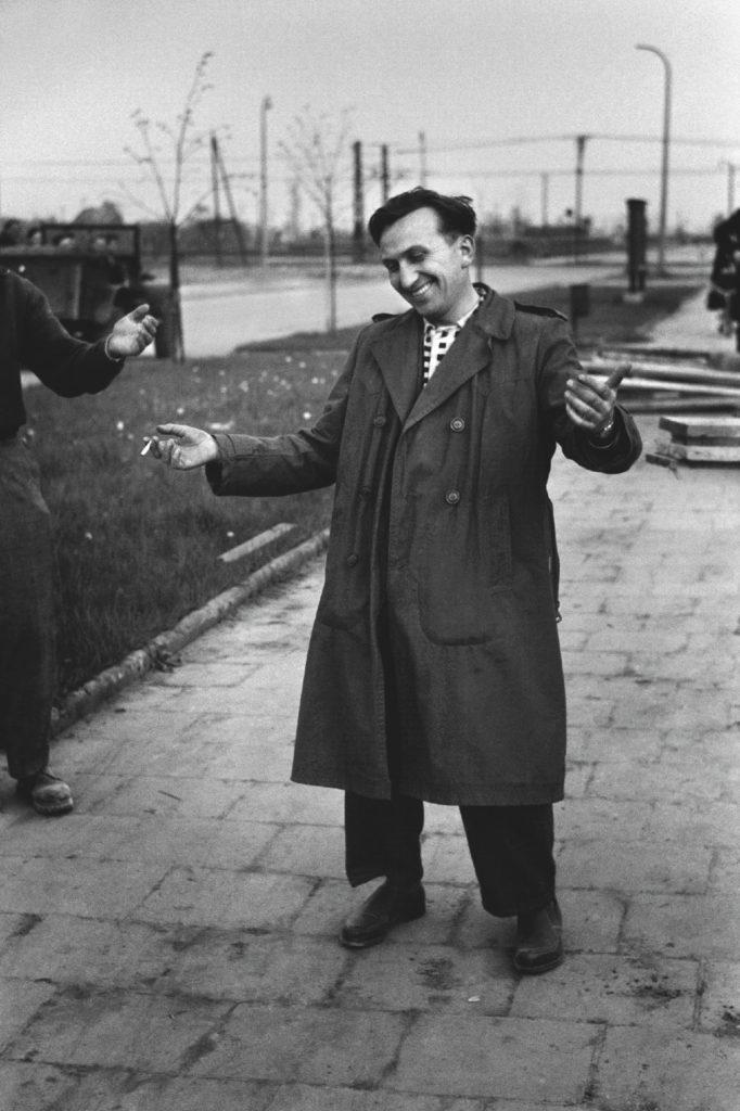 Uśmiechnięty mężczyzna w prochowcu rozkłada ramiona.