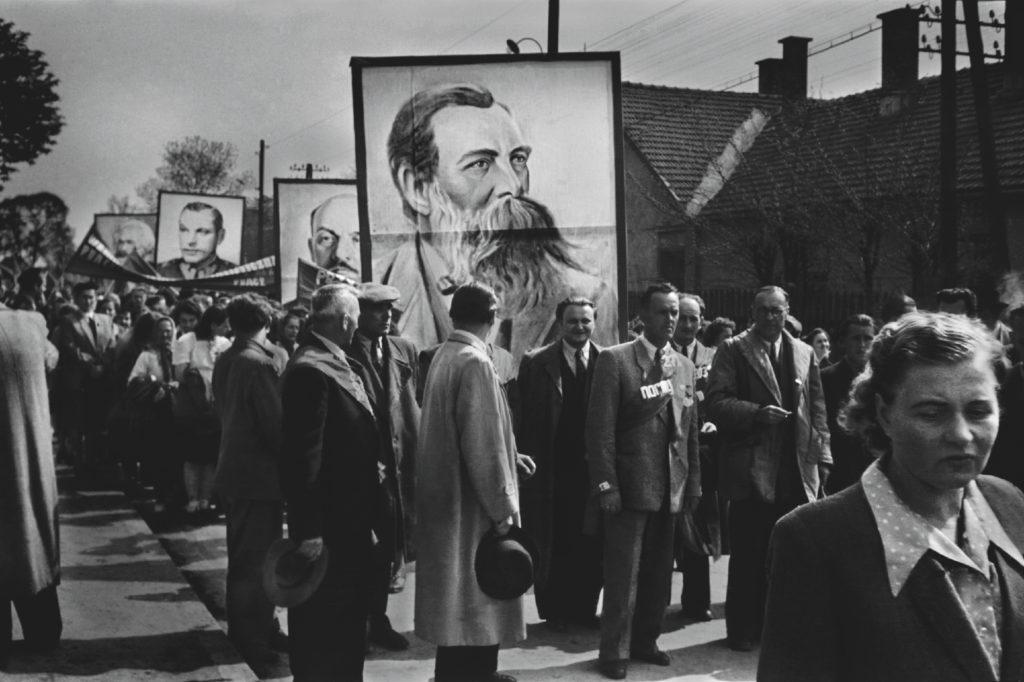Odświętnie ubrani ludzie niosą portret Engelsa.
