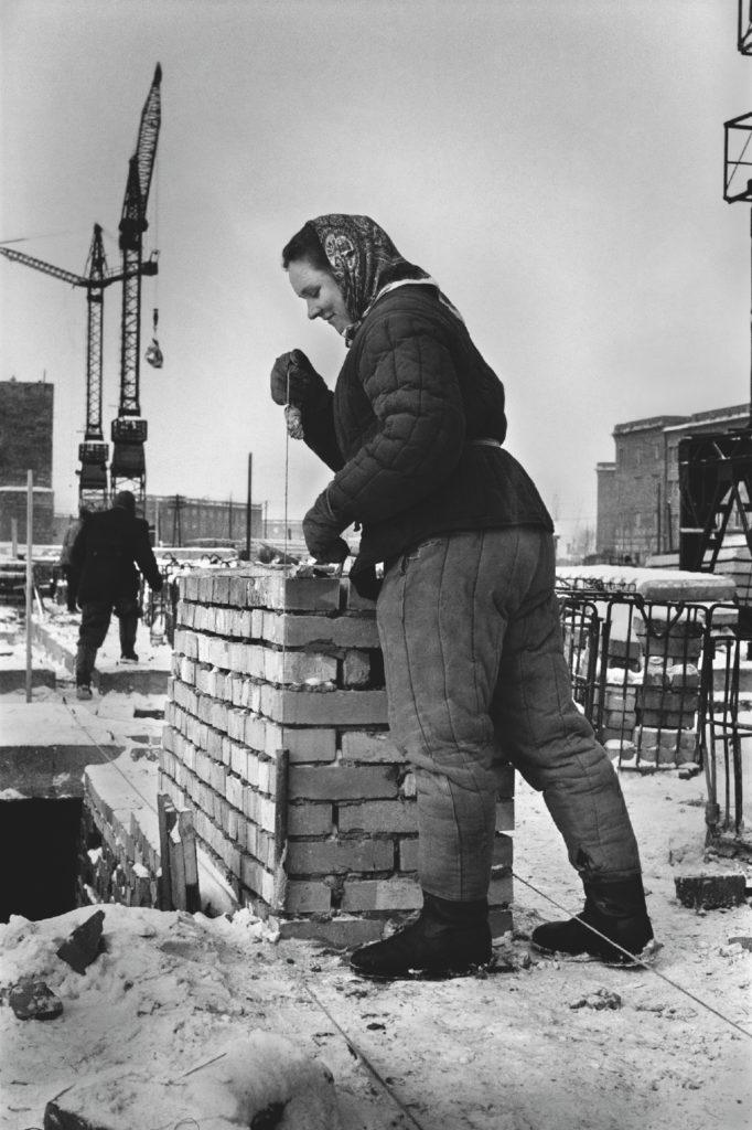 Kobieta w waciaku sprawdza pion budowanego komina.