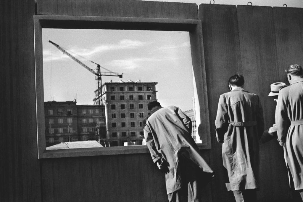 Mężczyźni w płaszczach oglądają prefabrykowaną ścianę okienną. W tle blok mieszkalny w budowie.