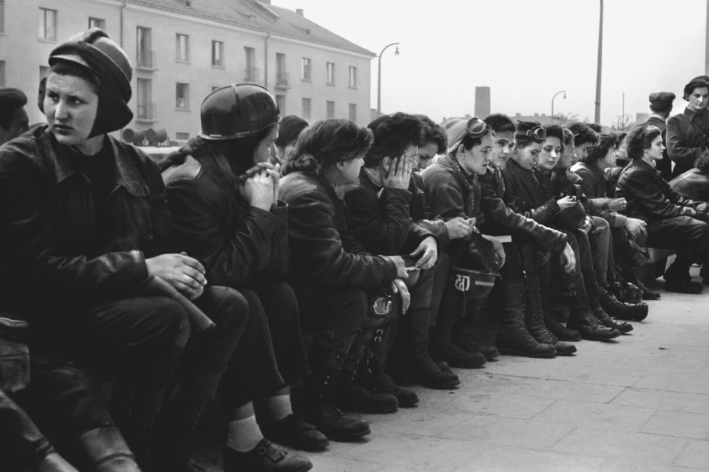Kobiety ubrane w stroje motocyklowe rozmawiają w oczekiwaniu na start rajdu, siędząc na długiej ławce.