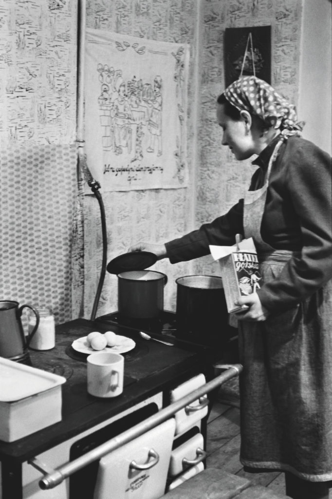 Kobieta w fartuchu i huście na głowie dogląda potrawy na kuchence.