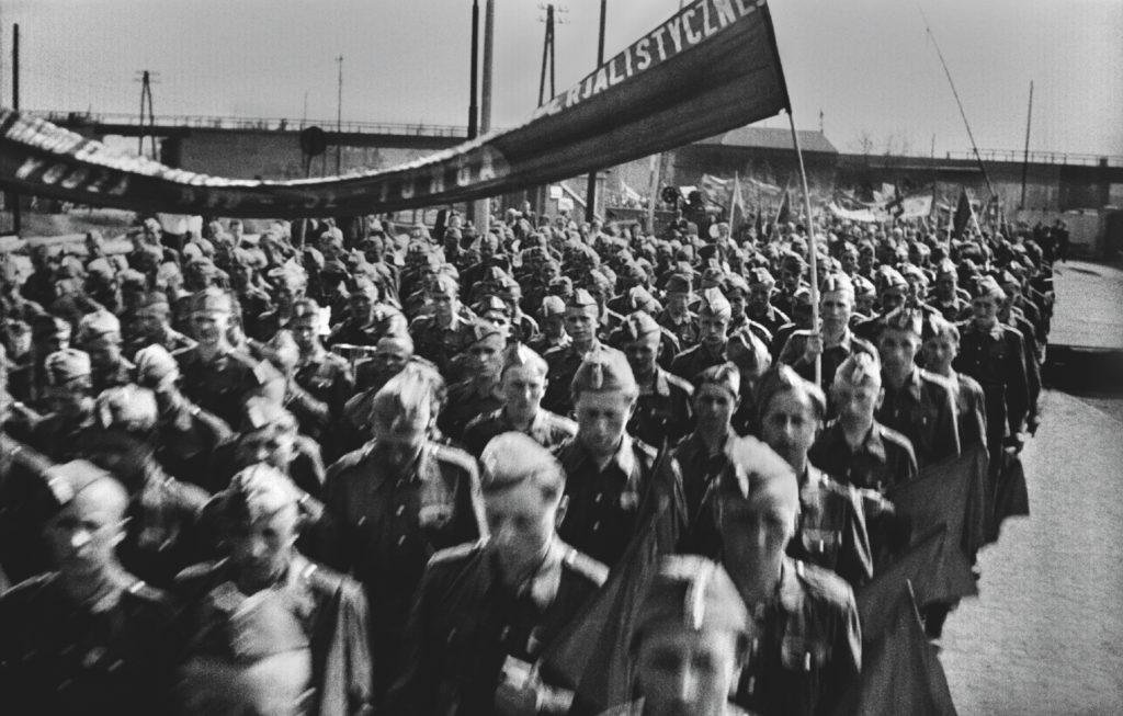 Młodzi mężczyźni w mundurach maszerują w szeregach niosąc propagandowe transparenty.