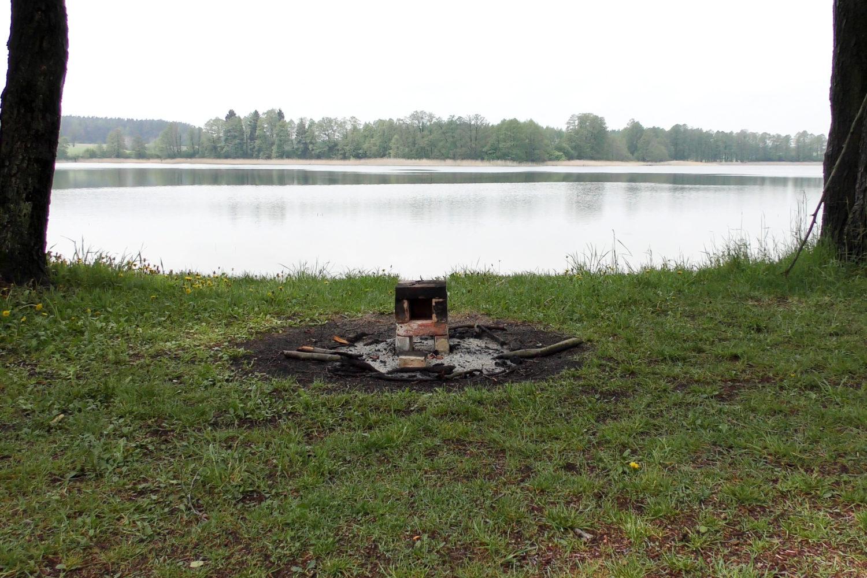 ślady dużego ogniska na brzegu jeziora ulokowanego na trawie pomiędzy drzewami. Pośrodku paleniska zbudowany z cegieł i gliny piec.