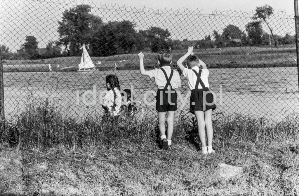 Dwóch chłopców w spodenkach na szelkach opartych o drucianą siatkę ogrodzenia obserwuje przez nią pływające po rzece żaglówki.
