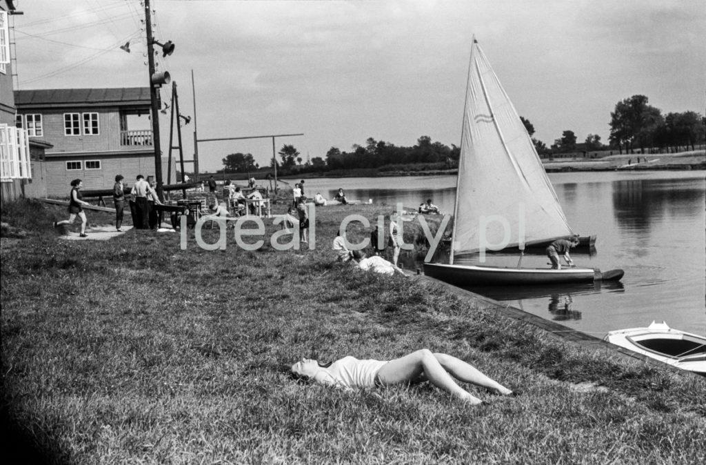 Kobieta w stroju kąpielowym opala się na pokrytym trawą brzegu rzeki, przy którym cumują żaglówki.