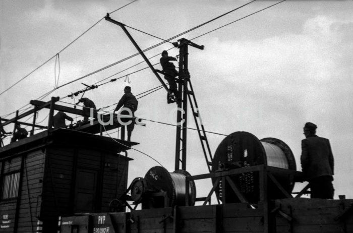 Installing a traction drive. 1950s.  Montaż trakcji kolejowej. Lata 50. XX w.  Photo by Henryk Makarewicz/idealcity.pl