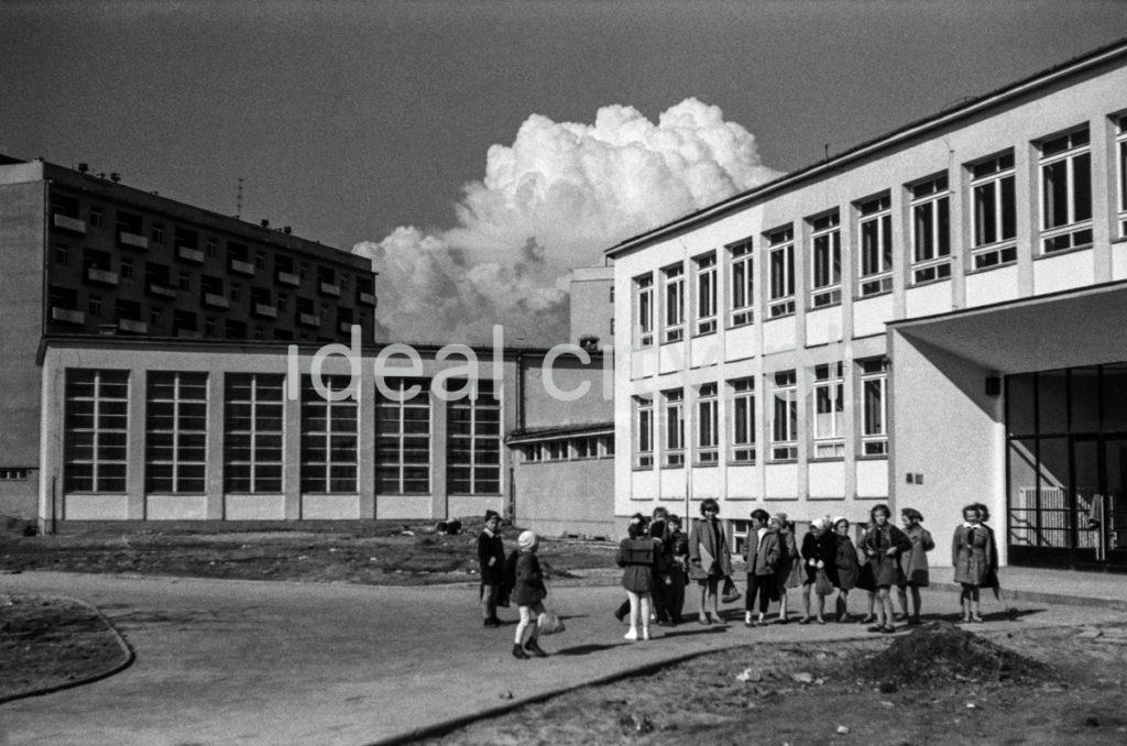 Dzieci przed modernistycznym pawilonem szkolnym, na niebie kłębiasta chmura.
