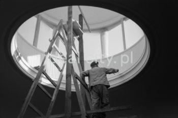 """Prace wykończeniowe w """"latarni"""" Teatru Ludowego na osiedlu C-1 (Teatralne). Początkowo miał on nazywać się Teatrem Kameralnym, ponieważ był planowany jako filia Teatru Wielkiego, który według planów miał stanąć na łąkach przy Placu Centralnym (projekt nie został zrealizowany). Teatr Ludowy został wzniesiony w latach 1954-1955 według projektu architektów Jana Dąbrowskiego i Janusza Ingardena. Ingarden wspólnie z Teresą Wąsowicz był także współautorem wnętrza projektu. Budynek wyposażono w marmurowe posadzki, kolumny, bogato zdobione kryształowe żyrandole, ozdoby stiukowe oraz tkaniny na ścianach. Amfiteatralna widownia liczyła ponad 400 miejsc. W projektach widoczne są elementy i detale naśladujące ptolemejski Egipt. Teatr rozpoczął działalność 3 grudnia 1955 roku przedstawieniem """"Cud mniemany, czyli Krakowiacy i Górale"""" Wojciecha Bogusławskiego. Lata 50. XXw.  fot. Henryk Makarewicz/idealcity.pl"""