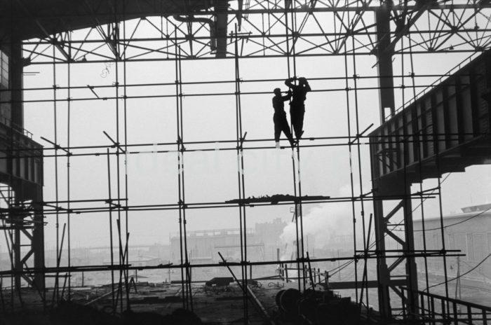 Lenin Metallurgical Combine, a production hall, putting up scaffolding, steelworks buildings in the background. 1960s.  Kombinat metalurgiczny im. Lenina, fragment jednej z hal produkcyjnych, montaż rusztowań, w tle widoczne zabudowania huty, lata 60. XX w.  Photo by Henryk Makarewicz/idealcity.pl