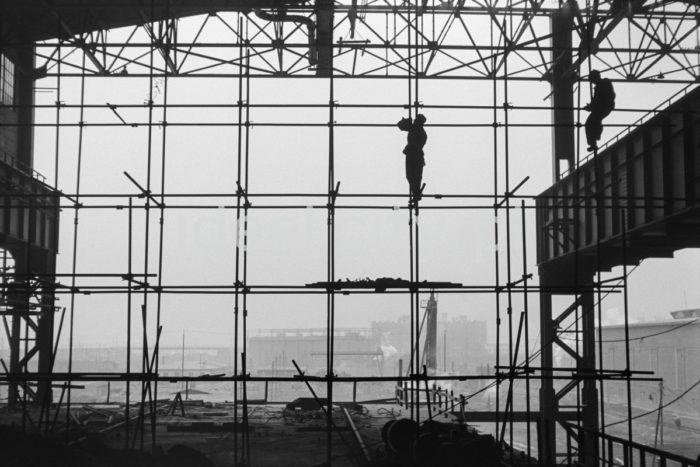 Kombinat metalurgiczny im. Lenina, fragment jednej z hal produkcyjnych, montaż rusztowań, w tle widoczne zabudowania huty, lata 60. XXw.   fot. Henryk Makarewicz/idealcity.pl