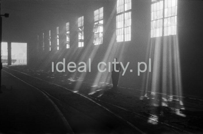 """Kombinat metalurgiczny im. Lenina, wnętrze hali Stalowni Martenowskiej, hala pieców martenowskich, lata 60. Stalownia Martenowska została uruchomiona w lutym 1955 roku, ostatni – dziesiąty piec – wybudowano w 1961 roku. Piece martenowskie używano do wytapiania stali z surówki odlewniczej i złomu stalowego. Piece pracowały przy udziale surówki płynnej, którą pobierano surówkowozami z mieszalników. Stal z pieców odbierana była z kadzi i rozlewana do wlewnic ustawionych na wozach podwlewnicowych, które po odpowiednim przygotowaniu były podstawiane przy pomocy trakcji kolejowej do hali rozlewniczej. Przeważającą większość produkcji stalowni martenowskiej przekazywano do walcowni wstępnych w stanie gorącym. W 1970 roku zmodernizowano Stalownię likwidując dwa piece starego typu. Na ich miejsce wybudowano nowoczesny, pierwszy w Polsce piec typu """"tandem"""".  fot. Henryk Makarewicz/idealcity.pl"""