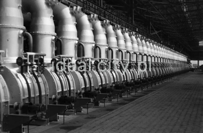"""Kombinat metalurgiczny im. Lenina, wnętrze hali Wydziału Walcowni Rur Zgrzewanych, lata 60. XXw.  uchomiono w 1960 roku. W 1973 roku uruchomiono drugi ciąg rurowni na Wydziale. Podstawowe urządzenia zakupiono w Republice Federalnej Niemiec, pozostałe wykonano w kraju według projektu biura projektowego """"Biprostal"""" w Krakowie. Pełny cykl technologiczny został zapewniony przez zainstalowanie takich urządzeń, jak walcarka formująca wraz ze zgrzewarką oporową, piec tunelowy, walcarka redukcyjna, prasy hydrauliczne do badania szczelności spoi rur, ocynkownia ogniowa rur, lakiernice do elektrostatycznego lakierowania, kilka zespołów gwinciarek rur, oddział produkcji i ocynkownia złączek oraz szereg urządzeń pomocniczych do sortowania, pakietowania i wiązania rur.  fot. Henryk Makarewicz/idealcity.pl"""