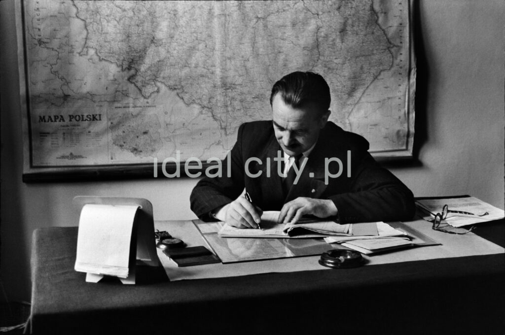A man in a jacket is writing something bent over a desk, behind him a map hangs on the wall.