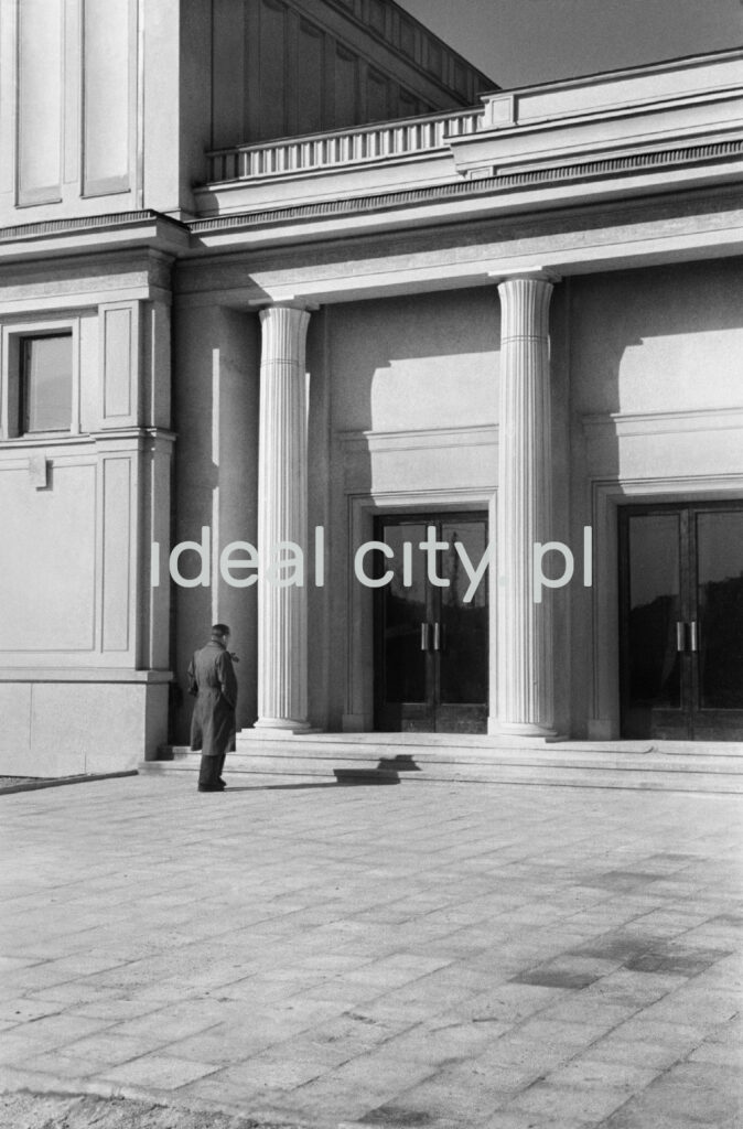 A man in a coat stands in front of the entrance to a monumental building with columns.