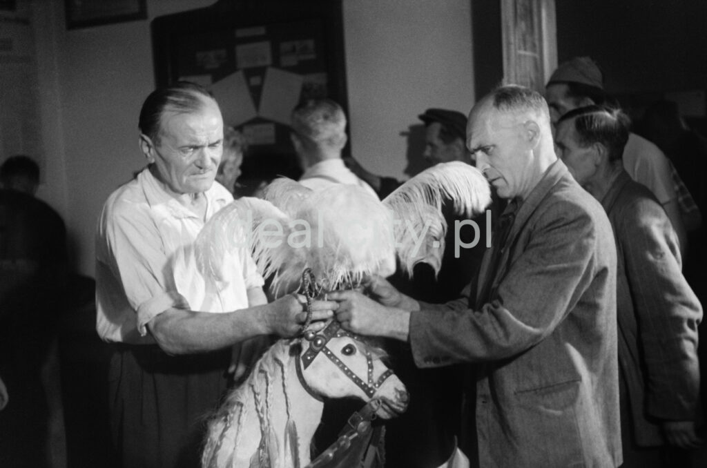 Two men are examining a theatrical prop in the form of a horse's head.