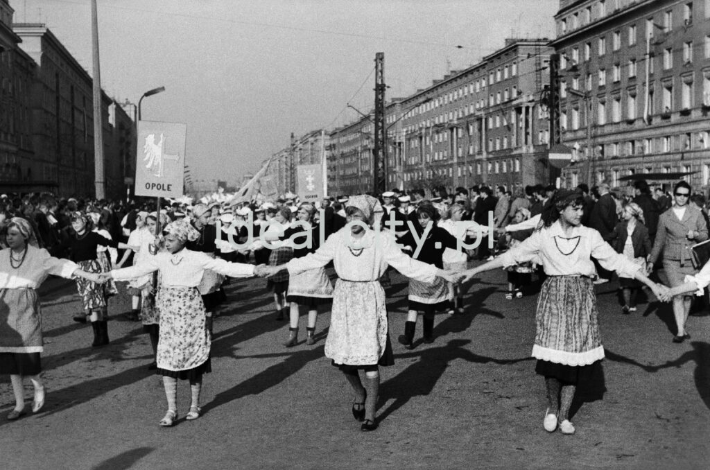 Girls in regional costumes march down a wide avenue holding hands, with apartment blocks on the left and right in the background.