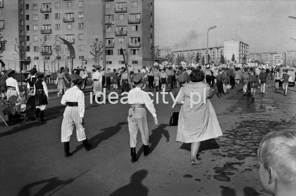 Two boys in regional costumes march with their mother in a coat on the tail of the march, in the background a block of flats.