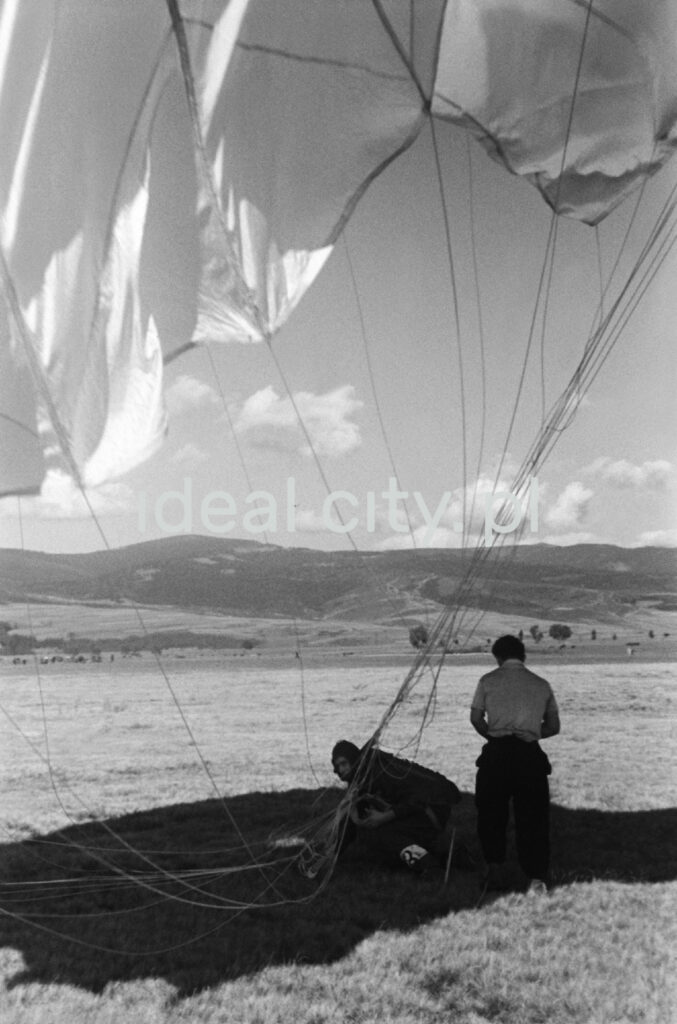 The man is standing in a meadow under the parachute canopy spread over him, mountain ranges in the background.